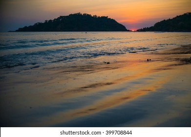 Orange summer sunset with black silhouettes of mountains on beautiful peaceful tropical beach, Goa, India