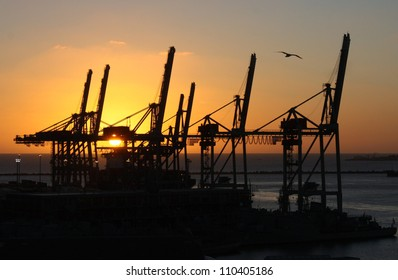 An orange sun going down and seen through the cranes in a port