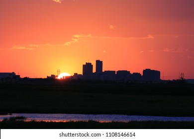Orange sun setting behind city skyline