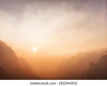 Orange Sun Setting Behind the Mountains.