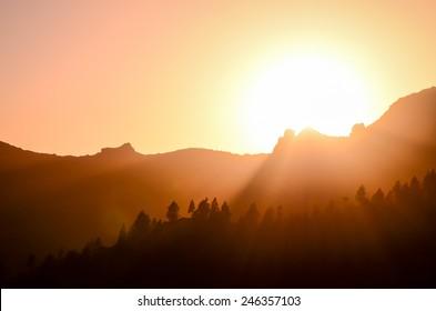 Orange Sun Setting Behind the Mountains