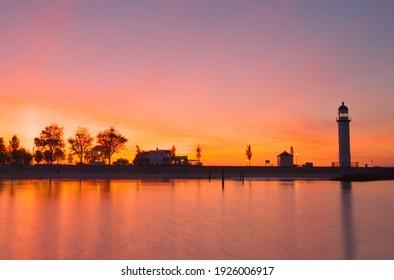 Orange sundown sky and lighthouse near sea. Nature landscape
