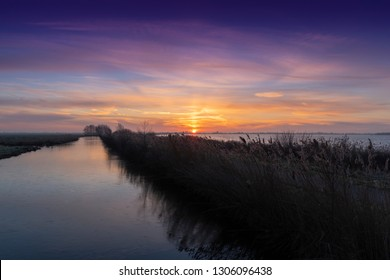 Orange sunrise above a lake and a ditch in  The Green Heart of The Netherlands, Europe.