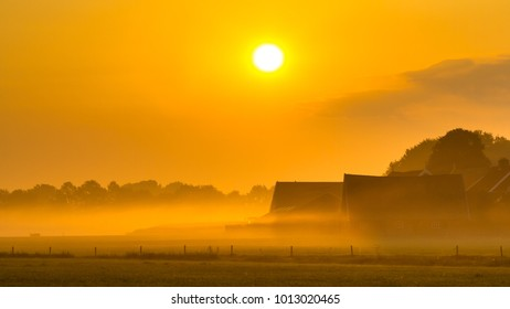 Orange sunrise over agricutural scenery with misty farm with barns and tractor in Twente, Netherlands