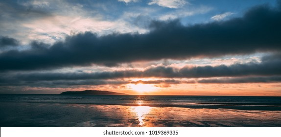 Orange sunrise with reflection on water anddark clouds on beach in Rush Ireland