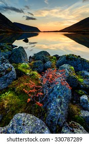 Orange sunset clouds over Alyavumchorr mount reflect in Tahtarjavr lake in Hibiny, with lichen covered rocks and dwarf birch on the foreground, Kola peninsula above the Arctic Circle, Russia