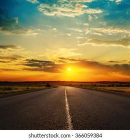 orange sunset in clouds over asphalt road
