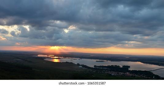 Orange sunset from the dark cloud over Moravian dam and vineyards. Panoramic photo.