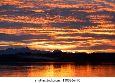 orange sunset at lake chiemsee with dramatic clouds