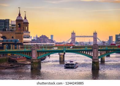 Orange sunset with London cityscape with Southwark bridge and tower bridge