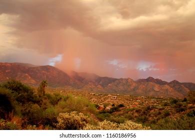 Orange Sunset monsoon storm with pink rain over the Tucson, Arizona Pusch Ridge Santa Catalina mountains during monsoon season