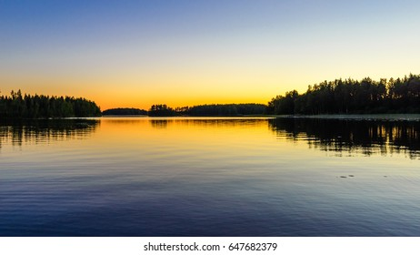 Orange sunset on the lake. Haukivesi lake, Saimaa lake system, Savo, Finland.