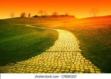orange sunset over hill with paved walkway