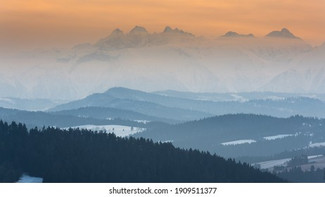 An orange sunset over the misty mountains