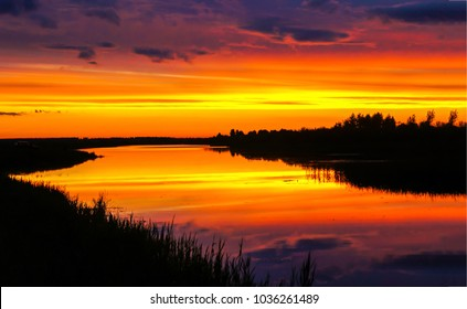 Orange sunset over river reflection in water landscape