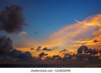 Orange sunset over sea, with dark clouds and rays of light