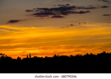 Orange sunset over silhouettes of village and trees