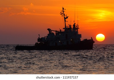 orange sunset over water with the silhouette of a tug boat