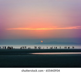 Orange sunset with silhouettes of people. Sun falls in the water gorgeous landscape