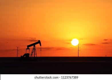 orange sunset sky and pump jack silhouette