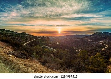 An orange sunset view across the horizon between hills and mountains from a distant mountain top view in Los Angeles, California.