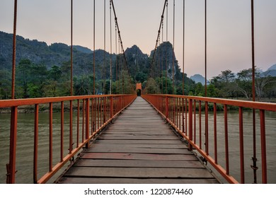 Orange suspension footbridge over the Nam Song River and scenic limestone karst mountains near the Tham Chang (or Jang or Jung) Cave in Vang Vieng, Laos, at sunset.