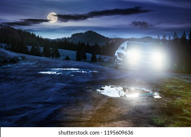 orange suv parked on the country road near forest in mountain at night in full moon light. beautiful autumn scenery. travel Europe by car concept