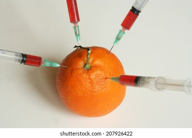 Orange and syringes. Genetically modified food.