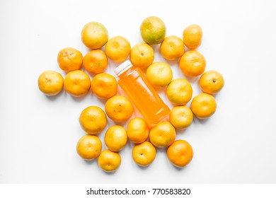 Orange tangerine / mandarin juice and a random bunch of tangerines with peel flat lay centered image on white background.