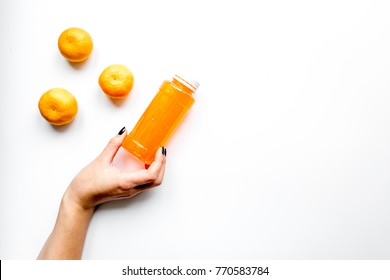 Orange tangerine / mandarin juice and three tangerines on white background flat lay mock up. Woman's hand holding a bottle of juice.