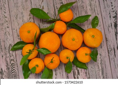 orange tangerines with green leaves are on the table