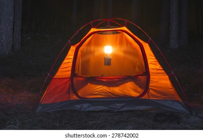 Orange tent in the forest at night