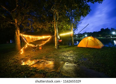Orange tent and hammock with decorative light At night in the forest