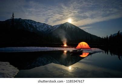 Orange tent on coast of lake at night.