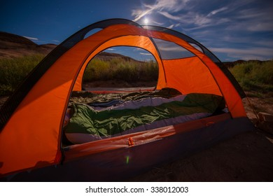 Orange tent and two sleeping bags bright night and a moonlight