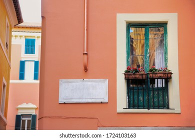 orange, terracotta old house in italy. Small balcony with flower pots