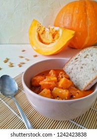 orange thick pumpking soup with a piece of bread and pumpkin in the background