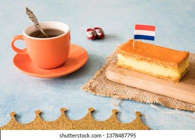 Orange tompouce, traditional Dutch treat with pudding and frosting on national holiday Kings Day (April 27th), in The Netherlands. With cup of tea, wooden shoes, Dutch flag and crown