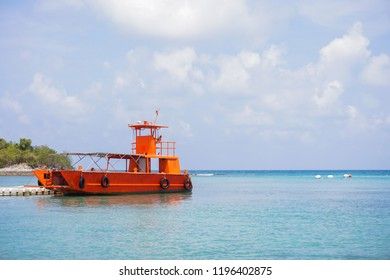 Orange tourist boat in blue sea ocean water
