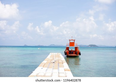 Orange tourist boat in harbor or port in blue sea ocen water