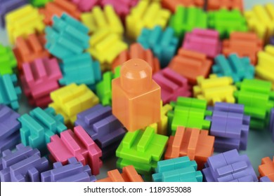 Orange toy building block on a pile of other toy blocks.