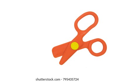 Orange toy scissors on white background.