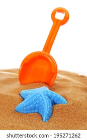 an orange toy shovel and a blue starfish-shaped mould on the sand, on a white background