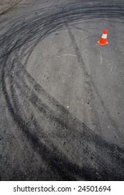 Orange traffic cone and round car drift skid marks