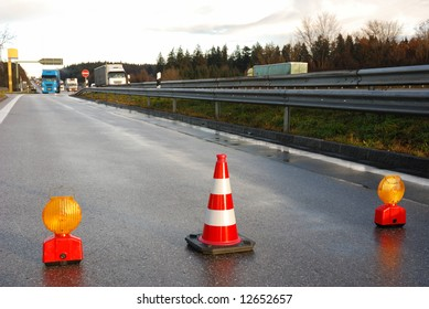 orange traffic cone and warning light on wet asphalt