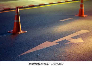 Orange traffic cones and white traffic sign on macadamized road at night.