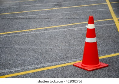 orange trafic cone on the parking lot, safety cone, rubber cone