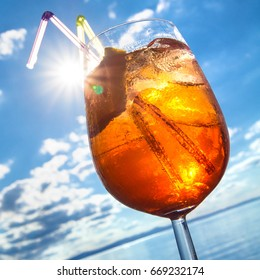 Orange transparent cocktail with ice cubes and straws in sunshine against blue sky; Refreshing summer drink; Relaxation on hot summer day; Summer holiday mood
