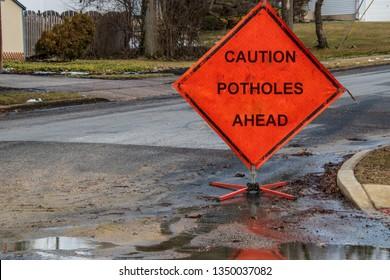 Orange triangular road sign on a small suburban street that says caution potholes ahead