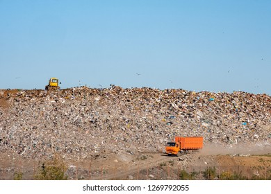 orange truck at the bottom and yellow tractor at the top of the dump, big dump and blue sky